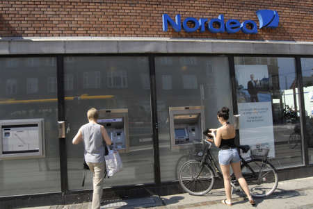 cash machine: COPENHAGENDENMARK _   Femaleconsumer cashing money at automatiuc cash machine at Nordea Bank 26 July 2012