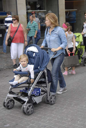 prams: COPENHAGENDENMARK _ Tourists with families and kids  mature and seniors and shoppers tourists with baby prams and women accepting summer babies on pedestrain street stroeget today on 2 August 2012