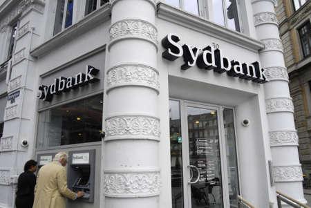 cashing: COPENHAGENDENMARK _  Consumer cashing money from Sydbank  automatic cash machine 10 August 2012          Editorial