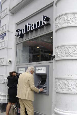 cash machine: COPENHAGENDENMARK _  Consumer cashing money from Sydbank  automatic cash machine 10 August 2012          Editorial