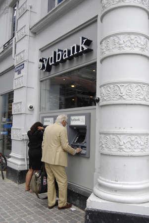 cashing: COPENHAGENDENMARK _  Consumer cashing money from Sydbank  automatic cash machine 10 August 2012