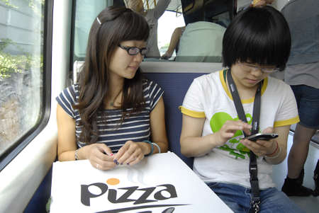 htc: COPENHAGENDENMARK _ Tow chiense females eat western Pizzaa and communicate with HTC Taiwan product HTC smartphone 13 August 2012       Editorial