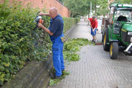 deere: KASTRUPCOPENHAGENDENMARK _Tow landscapers cutting hedge and landscaper use USA made tractor John  Deere 22 August 2012