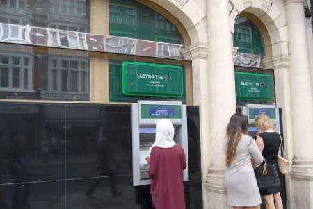 LONDON/ ENGLAND /UK _ Female cashing money at lloyds TSB bank automate money cash machine 10 Sept. 2012           Stock Photo - 15180882