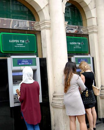 cash machine: LONDON ENGLAND UK _ Female cashing money at lloyds TSB bank automate money cash machine 10 Sept. 2012