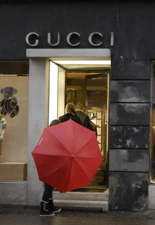 gucci store: COPENHAGENDENMARK _ Consumers in rain and walking some under umbrella by Gucci luxury store at stroget today 6 Oct. 2012
