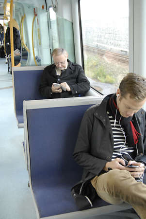 COPENHAGENDENMARK _ Metro computer traian male passenger texting via iphone spartphones during their journey 7 Oct. 2012       Editorial
