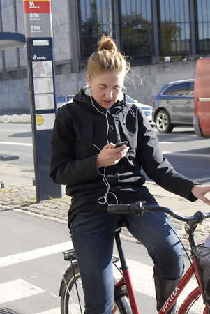 COPENHAGENDENMARK _   Female cyclest writing text messages and listen music same time on smartphone 12 Oct. 2012