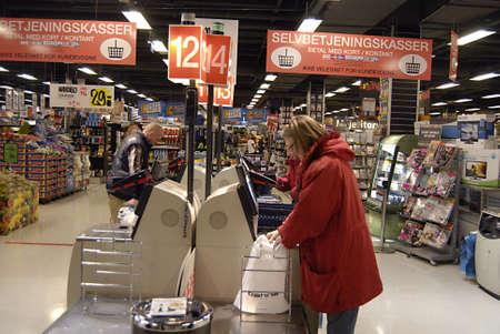 ediroial: Copenhagen  Denmark.  Danish consumers selv checking or self service at like united states of american in one of danish local food supermarket store 5 Nov. 2012
