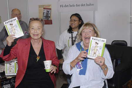 ediroial: Copenhagen  Denmark. Left in photo Gretelise Hom writer in red and Lone K�hlmann journalist and write at right in photograph with fdanish title fattigLus poor louse book writen by third writer at bogmesse 2012 or Copenhagen Book Fair 2012 at Bella Center Editorial
