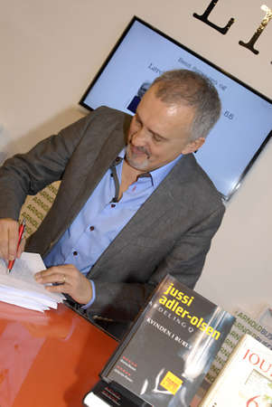 ediroial: Copenhagen  Denmark. Jussi Adler-Olsen author and writer signs his new book Journal 64,at Book fair 2012 (Bogmessen 2012)in Bella Center  his previous best seller Wom,an in House  10 Nov. 2012