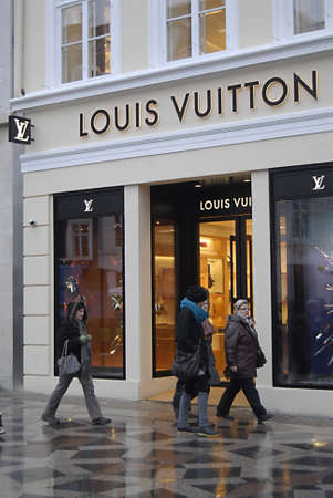vuitton: Copenhagen  Denmark. Christmas shoppers in rainyweather at stroeget passing by Louis Vuitton luxury store and Georg Jensen danish sliver smith store now Georg Jensen is own by Mideast investor from Bahrain today on 4 December 2012
