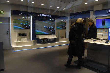 hi fi: Copenhagen  Denmark.  Couple in Samsumng smartytv smartphone and laptop center in local hi fi store  14 Dec. 2012