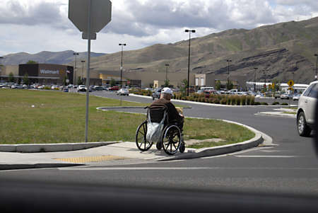 eldlery: CLARKSTONWASHINGTON STATE USA _Senior disable male while on wheel chair has cardbord sign for financial help  18 June 2012