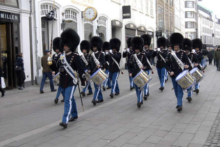 gaurd: Copenhagen  Denmark. Tourists photographing Danish Royql Queen Guard shile gaurd parade on stroeget today on woman day friday 8 March 2013