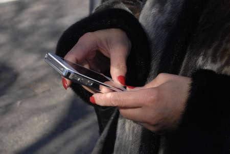 Copenhagen / Denmark. Femal checking bus timetable at apples iphone smartphone 3 April 2013