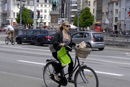 trafic: Copenhagen  Denmark._More and more young biker or cyclests use smartphone  to talk reading text message of eamils and listening music in trafic 27 May 2013