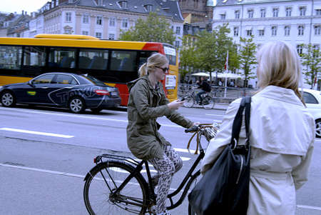 Copenhagen / Denmark._Female cyclest on smartphone talking listen music and reading emails or text messages 29 May 2013          Stock Photo - 19886177