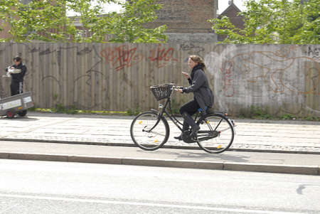 htc: Copenhagen  Denmark._Female cyclest on smartphone talking listen music and reading emails or text messages 29 May 2013