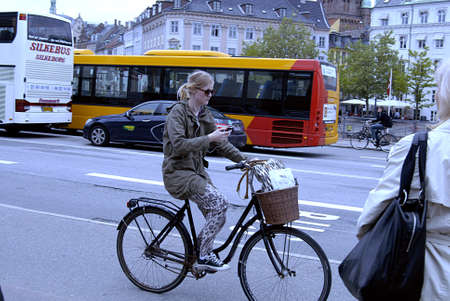 Copenhagen / Denmark._Female cyclest on smartphone talking listen music and reading emails or text messages 29 May 2013         Stock Photo - 19886179