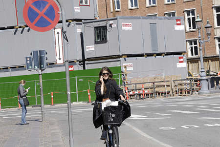 Copenhagen  Denmark.   _More and moe danmish women talk on smartphone while riding by bicycling in  trafic 6 JNune 2013