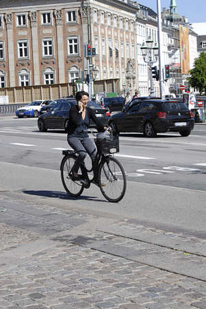 Copenhagen  Denmark.   _More and moe danmish women talk on smartphone while riding by bicycling in  trafic 6 JNune 2013       Redakční