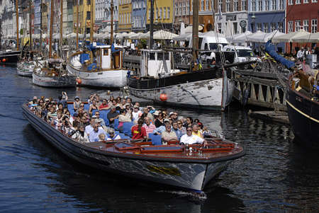 Copenhagen  Denmark.  View of Nyhavn canal boat tourists old house and food resatuarant 11 June 2013