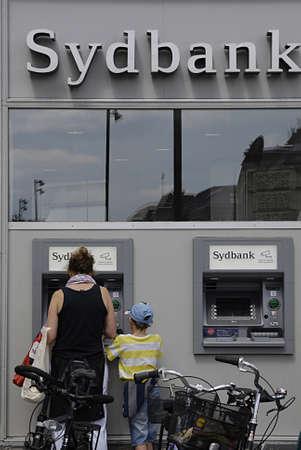 automate: Copenhagen  Denmark._Female bank consumer cashing money at Sydbank ATM or cash automate 24 June 2013