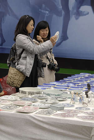 Copenhagen  Denmark. _Asian tourists when they visit Copenhagen they go to Royal Copenhagen store and they have small Royal Copenhagen shopping bags with trade mark Royal Copenhagen and they visit flea maket o yard where they see china procelains in town
