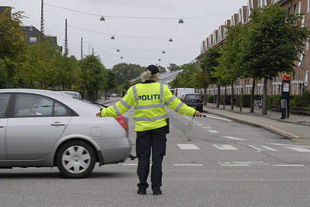 trafic: KASTRUPCOPENHAGENDENMARK _Danish female officer politi diretcing trafic may part of trafic polifce training or due to no trafic signal light scotgaard crossing  today on 2 July 2013        Editorial