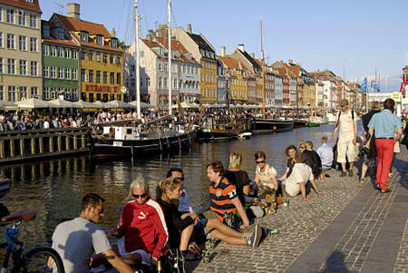 Copenhagen  Denmark.People enjoy july summer day while sun set over Nyhavn canal 11 July 2013