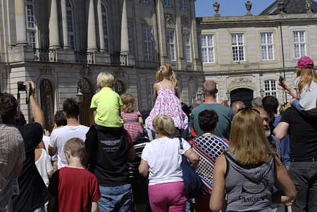 vacationers: Copenhagen  Denmark._Travellers and holiday maker on danish hot summer day 27C tourists at Aamalienborg Palace t aking photos of rotalk guards and travelers and vacationers on Nyhavn canal boat sailing and walking and eating  ice cream tourists with thei