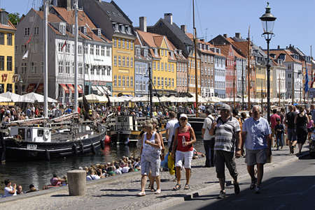 holiday maker: Copenhagen  Denmark._Travellers and holiday maker on danish hot summer day 27C tourists at Aamalienborg Palace t aking photos of rotalk guards and travelers and vacationers on Nyhavn canal boat sailing and walking and eating  ice cream tourists with thei