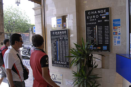 money exchange: PARISFRANCE _American travelers changing USA dollars bills to Euro at French Money Exchange  today on 22 July 2103