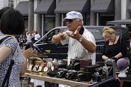 Copenhagen  Denmark. _Danish man   explains to aisan travelers  about old classic film camera at saturdays flea market at Kongens Nytorv today on 27 July 2013