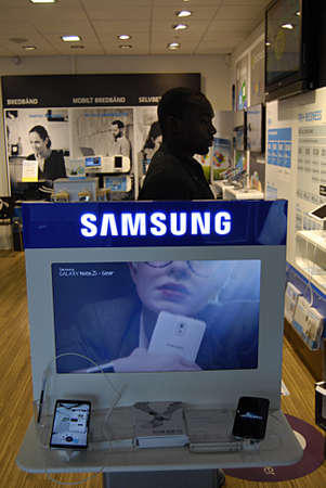 Copenhagen / Denmark.  22 October 2013_Consumer inspects samsung products at telecom store      Stock Photo - 23003818