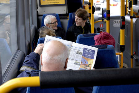 mx: Kastrup Denmark-  14 November  2013  _Man reading Metro Express MX free paper while rding bus