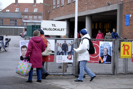 Kastrup /Denmark-  19 November  2013  _Danes rushing to polling station to cast thier votes for city councils and counties region at thier slected polling stations most of polish stations are locat in schools here this polling station is on Amager island  Stock Photo - 23817765