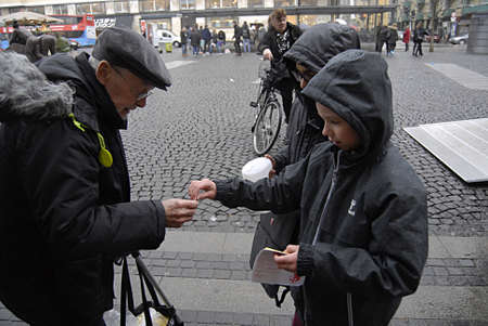 eldlery: Copenhagen Denmark- 04  December   2013  _   Eldlery man buying  christmas hearts from children office sticker for 2 dkr b�rnenes konto 2kr     Editorial