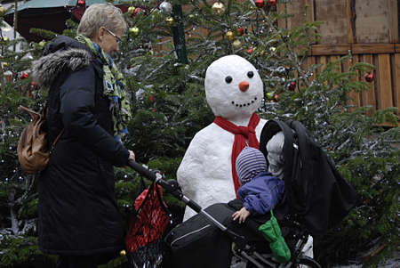 grand child: Copenhagen Denmark- 10  December   2013  _ Grand mother with grand child at christmas market with snow man