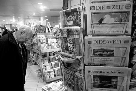 news stand: Copenhagen Denmark-  21  December  2013 _Senior male studing news at news stand