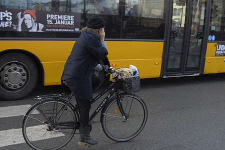 trafic: COPENHAGEN Denmark-  3 January 2014 _Female bicyclest talks on smartphone while riding on bicycle in trafic