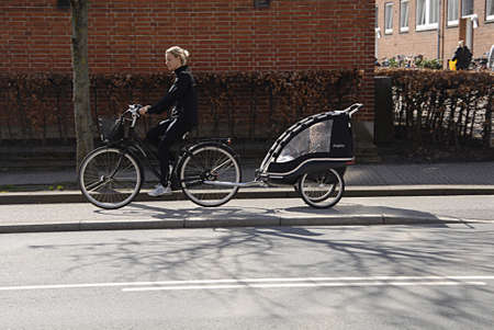 kastrup: KASTRUP COPENHAGEN DENMARK- Danish famiy mother transport child bu bicycle abd bike trolley        12 April 2014