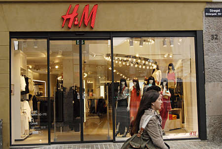 hm: COPENHAGEN DENMARK-  Young couple walk by H&M swedish chain store on stroeget        21 April 2014