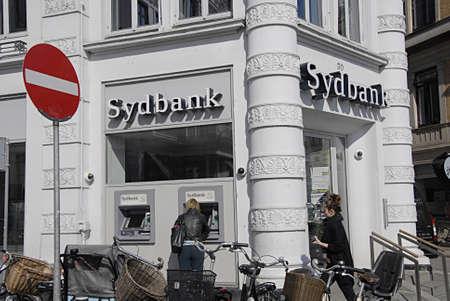 cashing: COPENHAGEN DENMARK-   Female cashing using atm at Sydbank  at kongens nytorv       23  April 2014