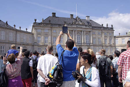 royality: COPENHAGEN DENMARK-Trvelers with their cameras iphone and ipad gether at Aamlienborg Palace royal guards change thought H.M.The Queen Margrethe II is not in palace and there is no fanfair during royal guard change during summer          17 July  2014
