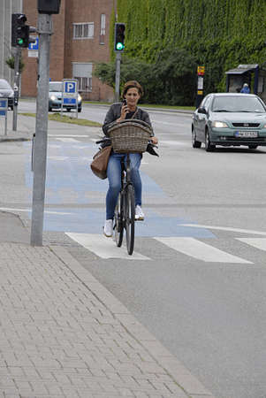 trafic: COPENHAGEN DENMARK- BFemale bike rider talking on smartphone in trafic          14 July  2014   Editorial