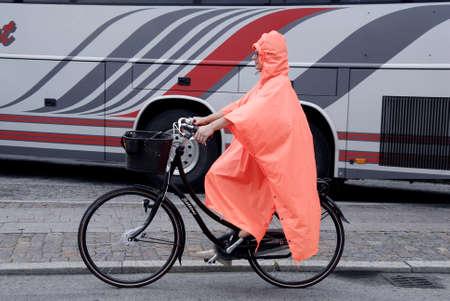 hot summer: Ciclista COPENHAGUE  DINAMARCA-Mujer en bicicleta bajo la lluvia hoy en Wedesday despu�s de semanas de verano muy calientes 30 de julio 2014 Editorial