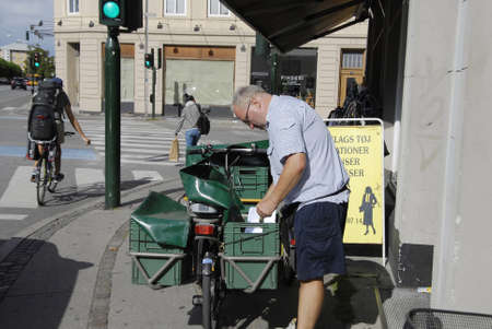post man: COPENHAGEN DENMARK- Danish post man delivers mail on saturday         16 Auguest  2014
