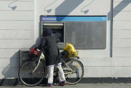 cashing: COPENHAGENDENAMK_   Female bikeris  cashing money at automat  at banknordik automat          19 September 2014